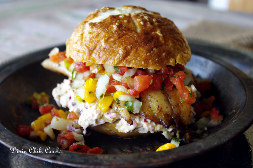 Blackened Tilapia with Buffalo Slaw and Mango Salsa on a Pretzel Bun